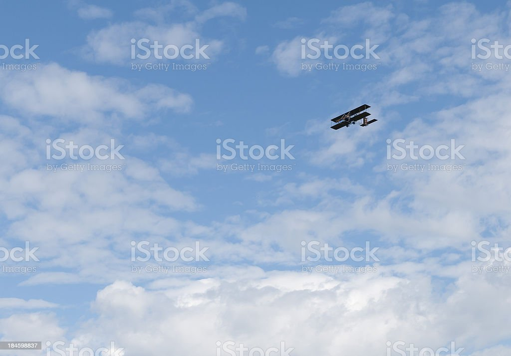 Wright Brothers Plane Replica Flying above Puffy Clouds stock photo