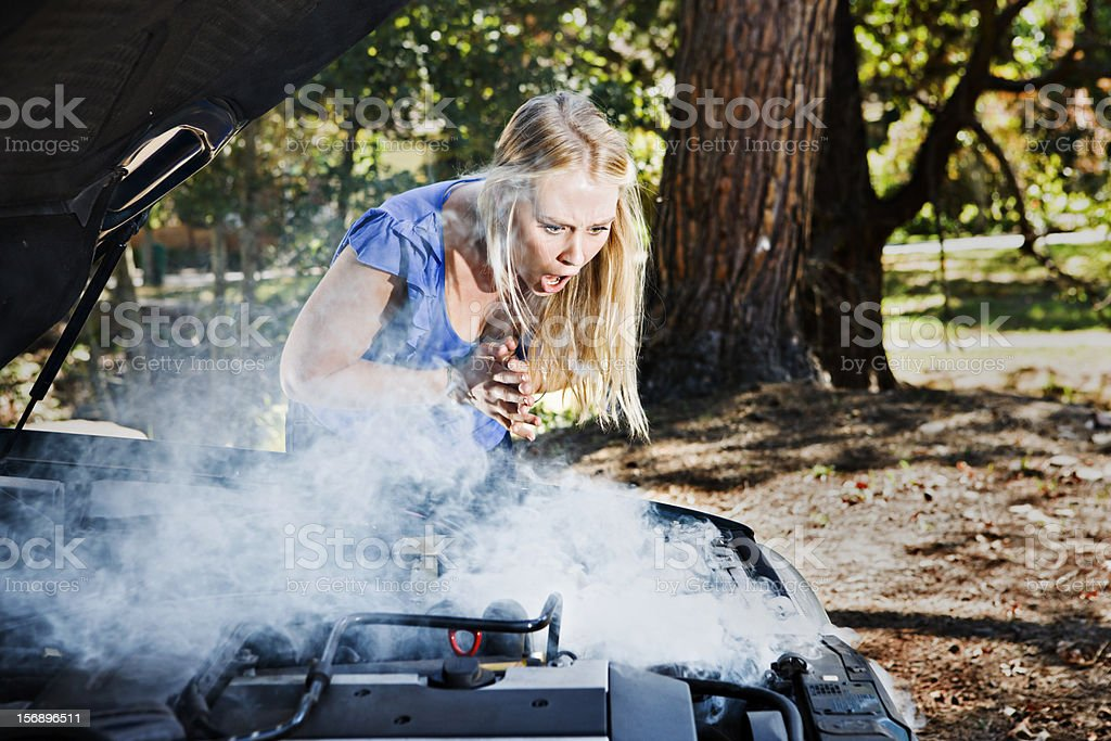 Wringing her hands, pretty blonde gasps at smoking car engine royalty-free stock photo