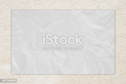 istock Wrinkle recycle paper on wood board. 497098669