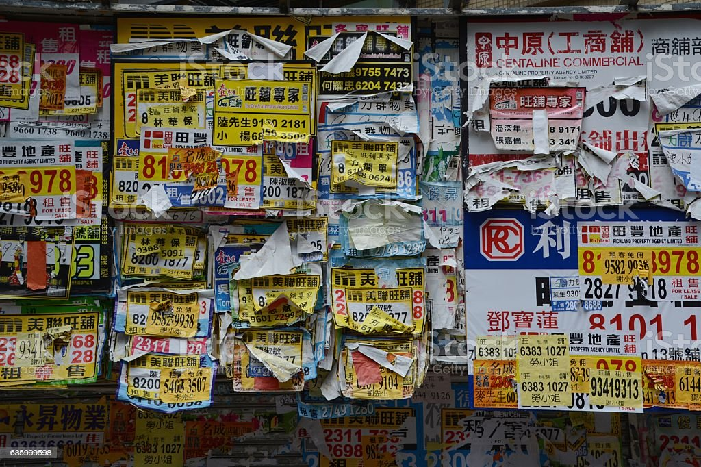 Wrinkled advertisements on a wall in MongKok district, Hong Kong stock photo