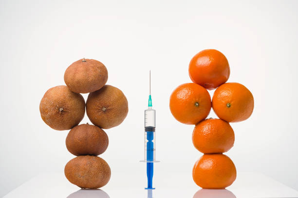 Cтоковое фото Wrinkled dried, smooth elastic tangerines in a female form and the syringe