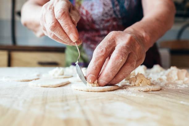 les mains des grands-mères ridée mettent le remplissage dans la pâte. fermez la vue. - seulement des femmes seniors photos et images de collection