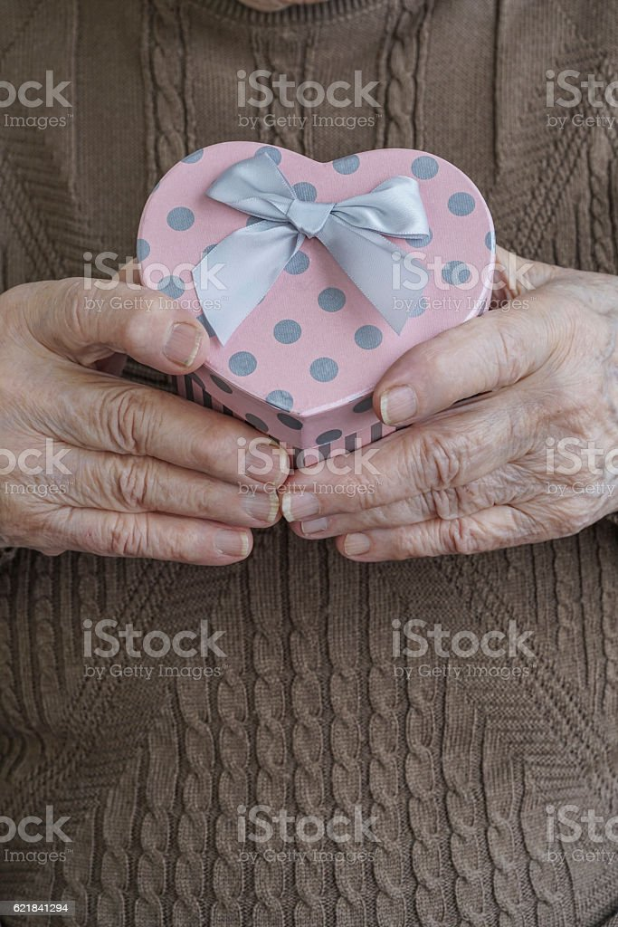 wrinkled hands holding a heart shaped gift stock photo
