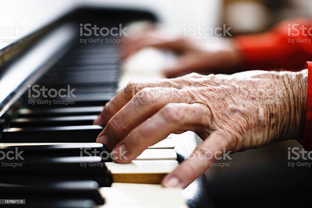 Wrinkled hands of an old person play the piano stock photo