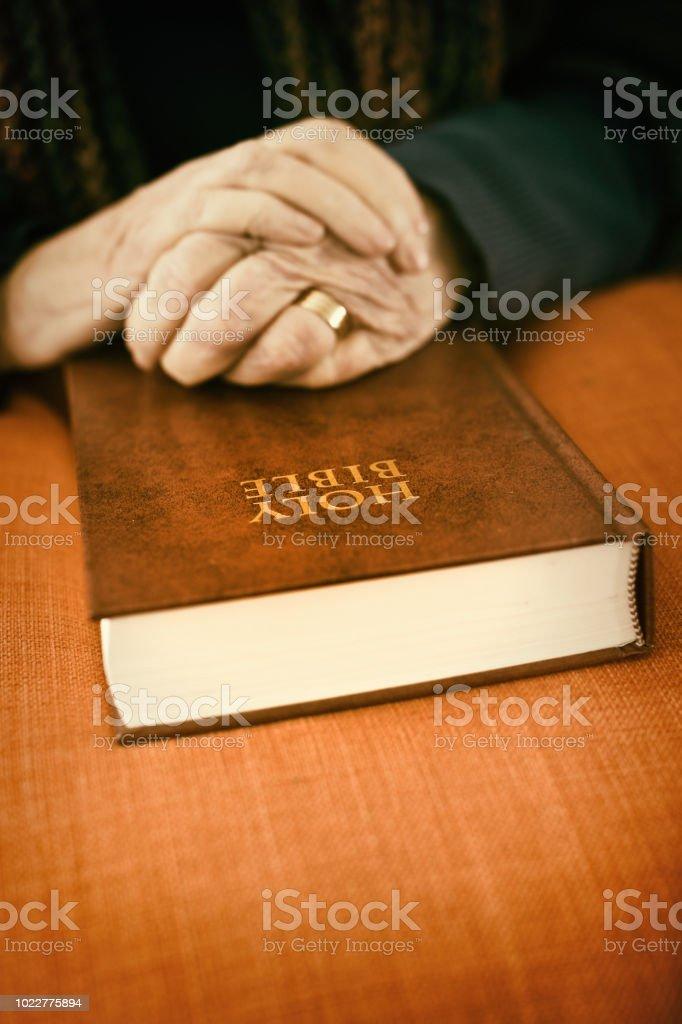 Wrinkled Hands Of Old Woman Folded In Prayer On Bible Stock