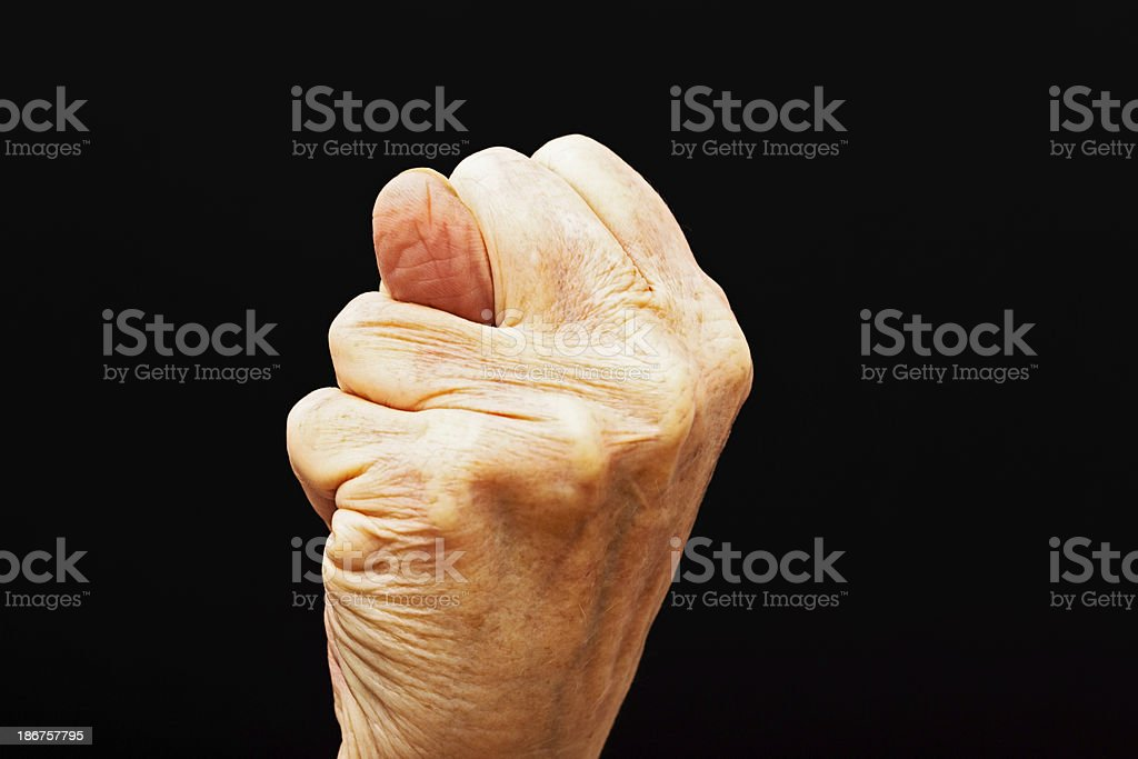 Wrinkled old hand makes obscene 'fig' gesture royalty-free stock photo
