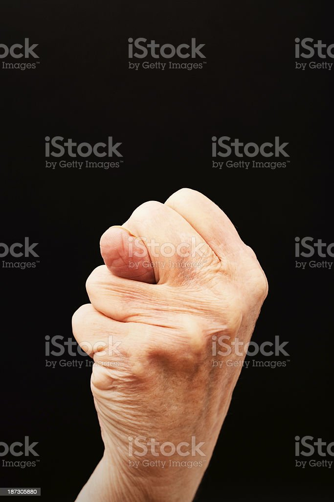 Wrinkled old hands gesture obscenely against black royalty-free stock photo