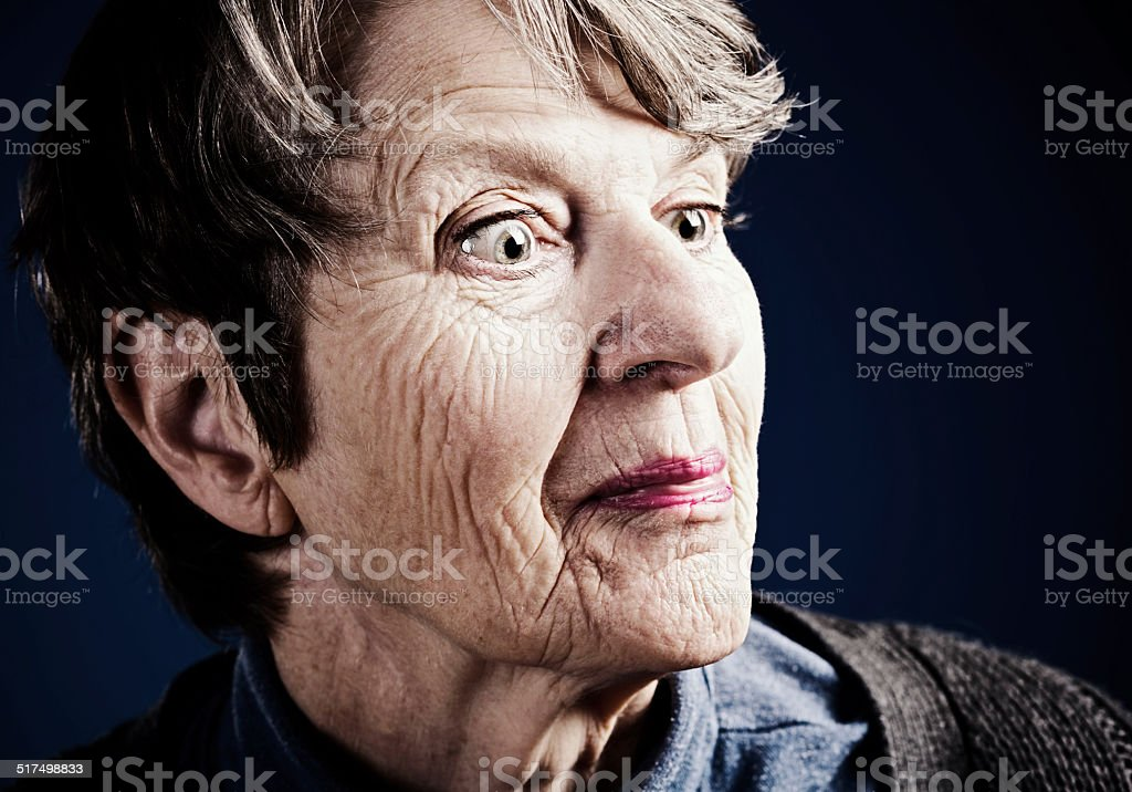 A wrinkled old woman smiles with her head cocked as she listens to or...