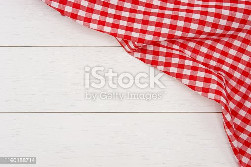 istock Wrinkled red gingham fabric on rustic white wood plank background. 1160188714