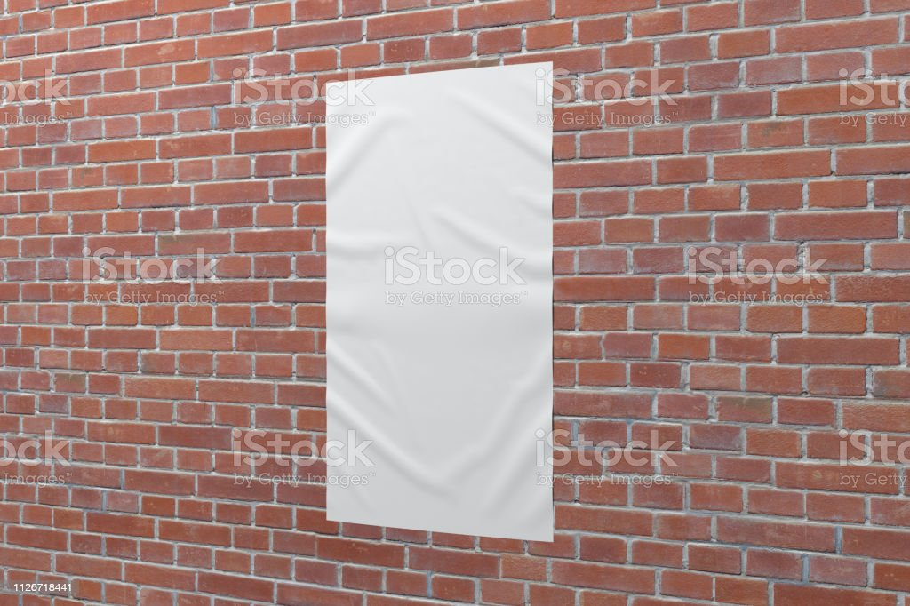 Blank vertical wrinkled street poster on brick wall. With clipping...