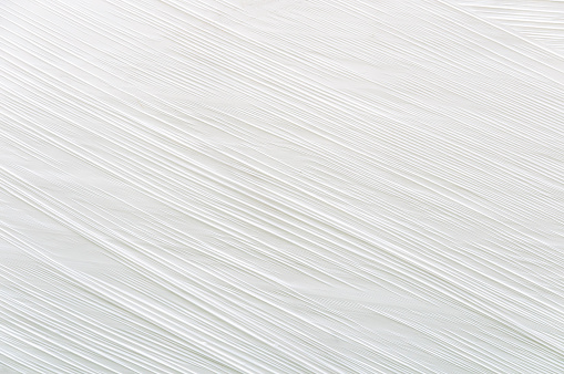 Close up of a white plastic film or tarp surface. Diagonal ripples or wrinkles.  Horizontal orientation. The image has been shot full frame and close up. Very interesting for backgrounds. The dimensions of the photo are 3189 px x 2118 px