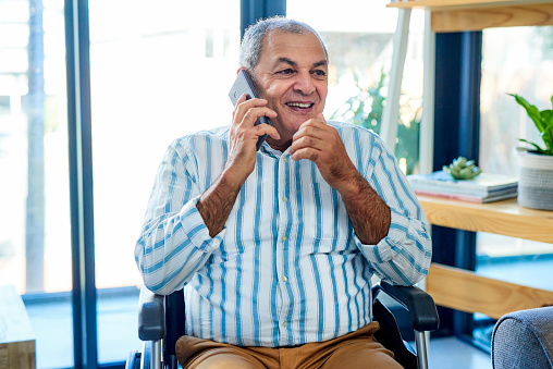 Shot of a wheelchair bound senior man talking on a mobile phone in the living room of his apartment