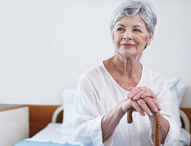 Wrinkles should merely indicate where smiles have been Shot of a senior woman leaning on her wooden walking stick fragility stock pictures, royalty-free photos & images