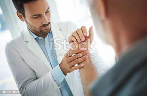 Closeup of a mid 30's doctor examining a senior male patient with injured wrist. The doctor is slowly moving and rotating patient's hand in order to determine the exact cause.