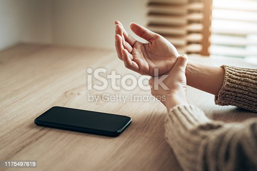 Woman holding her wrist pain from overuse smartphone.
