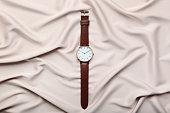 Wrist watch on beige satin background