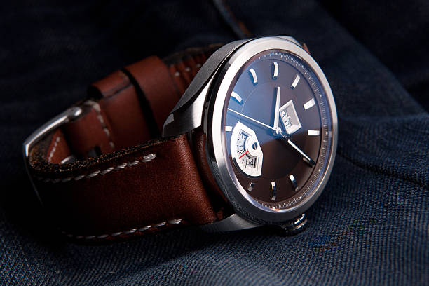 Wrist watch on leather strap on jeans background Wrist watch on leather strap on jeans background luxury watch stock pictures, royalty-free photos & images