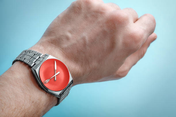 Wrist watch on man's hand. Plate, knife and fork on clock face. Concept of intermittent fasting, lunchtime stock photo
