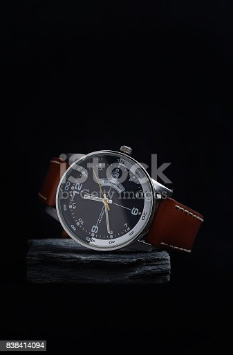 istock Wrist watch with a black dial on a gray stone with a dark background. 838414094