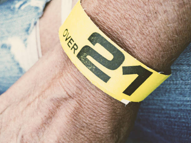 Wrist with yellow wristband: Over 21 stock photo