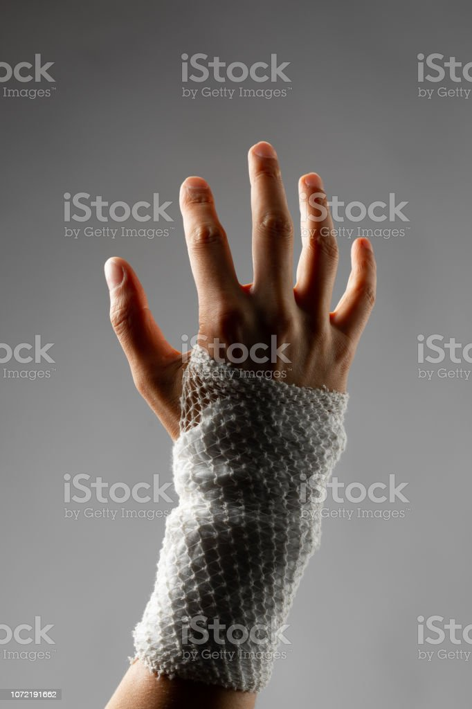 wrist wrapped with healing bandage, gray background