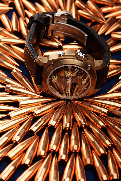 Wristwatch on bullets stock photo