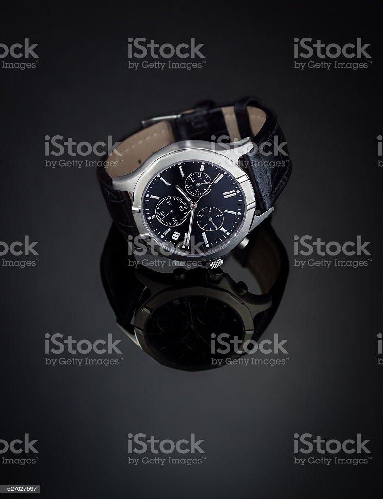 Wristwatch on reflective surface stock photo