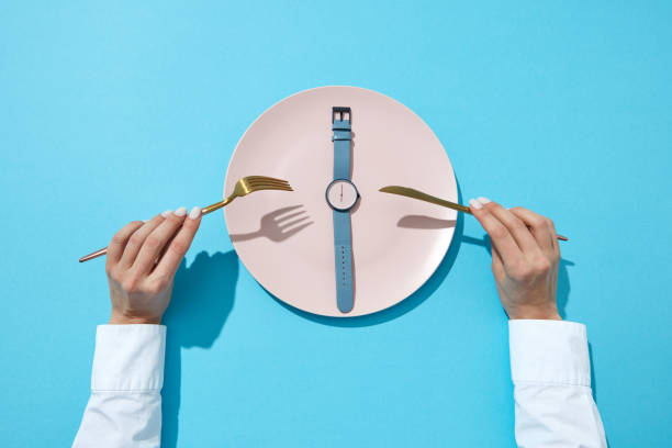 Wristwatch with six o'clock and woman's hand with fork and knite on a blue background. Time to lose weight, eating control or diet concept. Flat lay. stock photo
