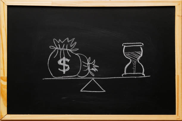 write sand clock or hourglass symbol and dollar bagson a balance scale in equal position on blackboard with chalk. financial concept : time value of money, asset growth over time, depicts investment in long-term equity for more money growth - depositor stock pictures, royalty-free photos & images