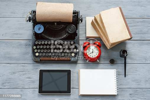 Typewriter, red alarm clock, blank page notepad, stack of books and modern digital tablet on gray wooden background.