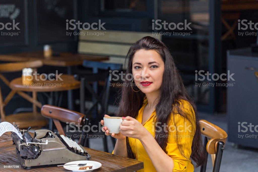 writer female with long dark hair, wearing yellow shirt and brown...