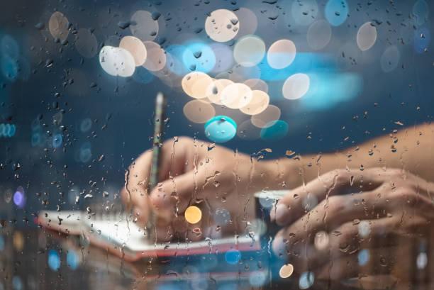schriftsteller in einem café. blick durch das fenster. regentropfen auf glas. - drehbuchautor stock-fotos und bilder