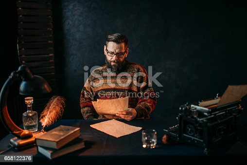 655113470 istock photo Writer in glasses reading his literature text 658122376
