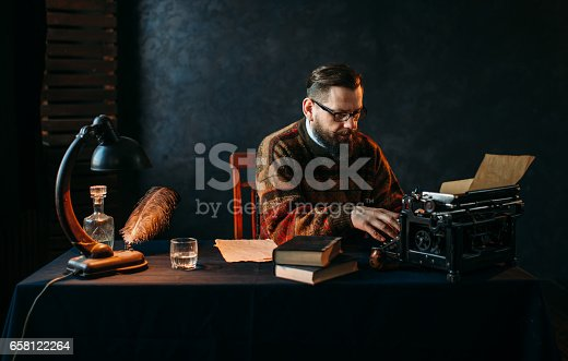 655113470istockphoto Writer in glasses typing on vintage typewriter 658122264