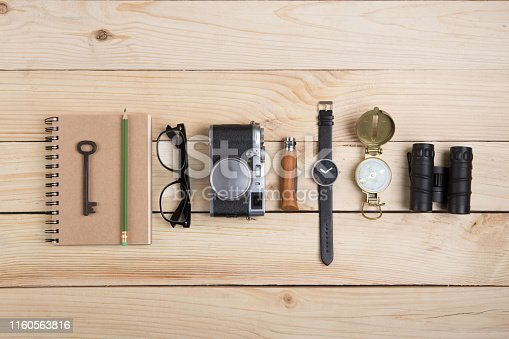 Writer, journalist or traveler desk notepad and photo camera on the wooden background