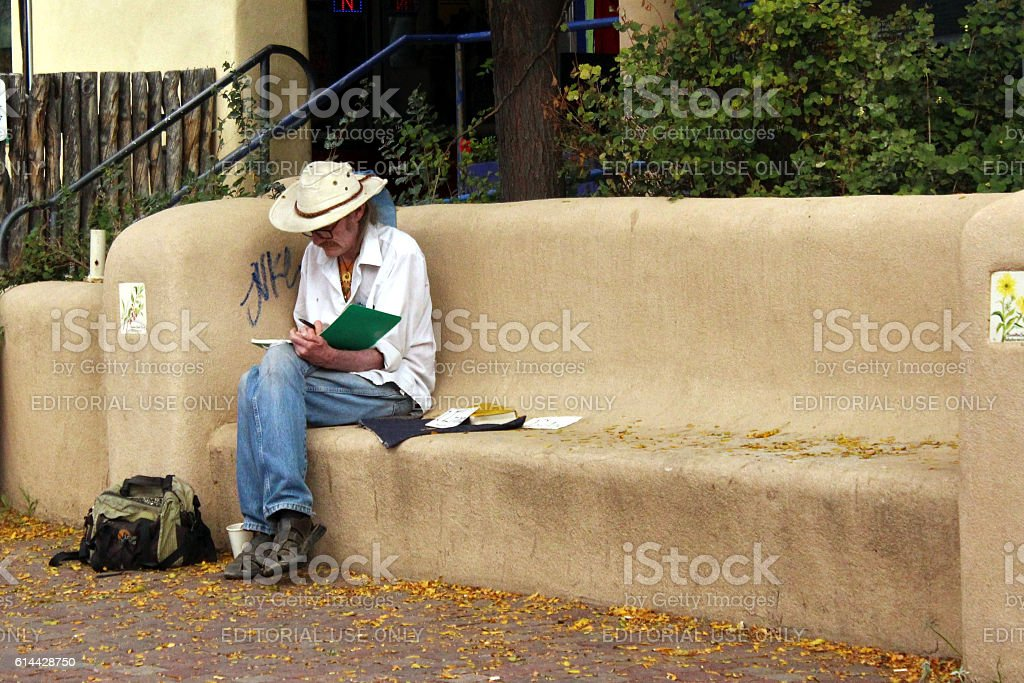 Writer sitting outdoors on adobe bench. stock photo