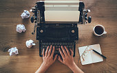 Top view of writer typing on vintage typewriter with crumpled papers around. Inspiration problem concept