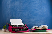 writer's workplace - crimson typewriter and books on blue blackboard background