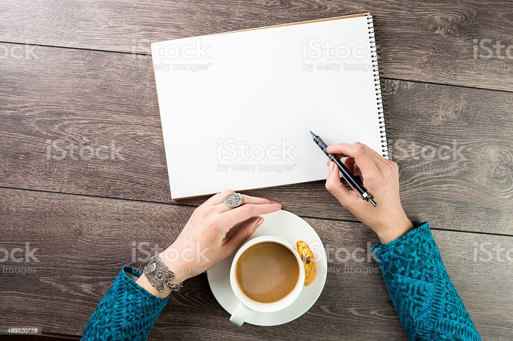 writes in a skechbook stock photo