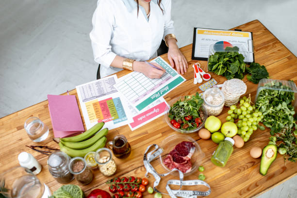 Writing a diet plan on the table full of healthy food Dietitian writing a diet plan, view from above on the table with different healthy products and drawings on the topic of healthy eating dieting stock pictures, royalty-free photos & images
