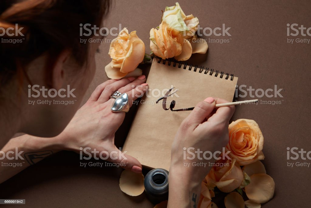 Writing a love letter with roses stock photo