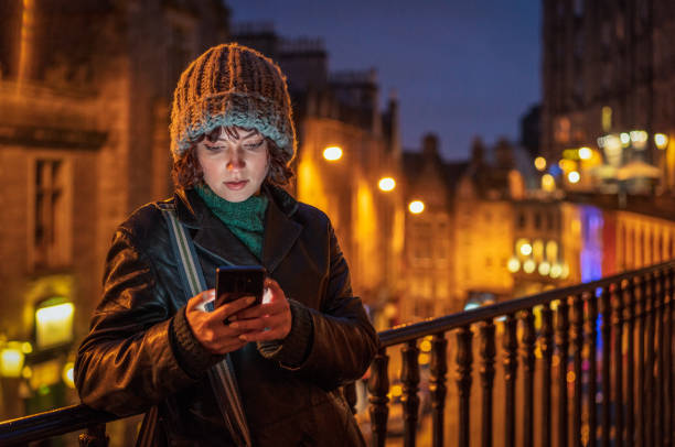 Writing a smart phone message alone in the city at dusk A young woman concentrates as she types a message on her smartphone at night, with her face illuminated by the device's screen. edinburgh scotland stock pictures, royalty-free photos & images