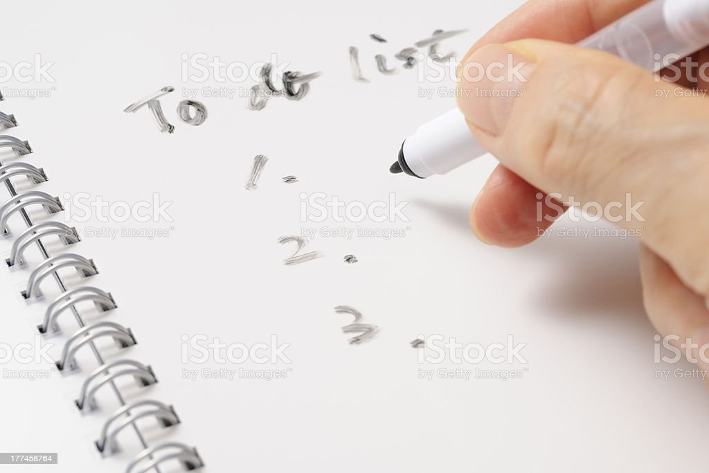 Writing a To Do List on spiral notebook royalty-free stock photo
