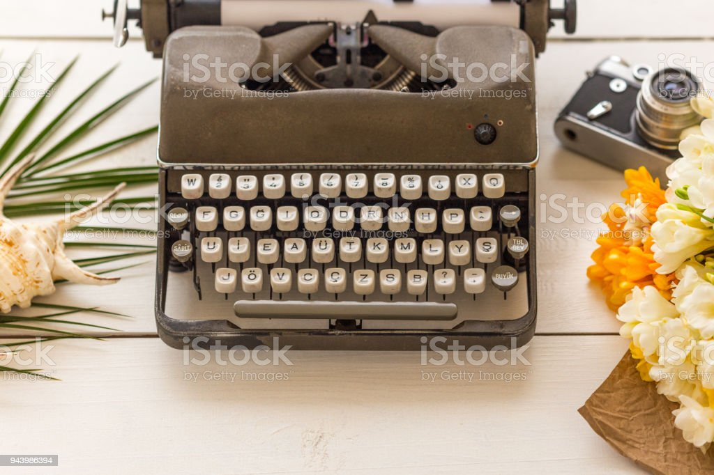 Writing and freelance concept. Retro typewriter, flowers, vintag stock photo