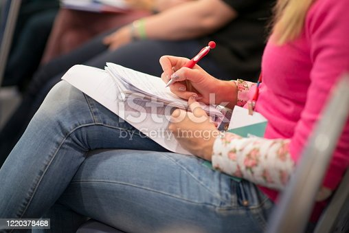 1028234706 istock photo Writing at a business conference. 1220378468