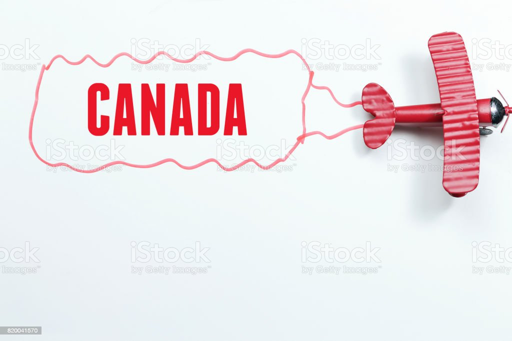 writing Canada red toy airplane with talk bubble on white background. Business holiday and travel concept stock photo