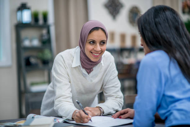 Writing Down Ideas Two Muslim women are working in their home office.   They are having a meeting. One woman wearing a head scarf is writing in a notebook. citizenship stock pictures, royalty-free photos & images