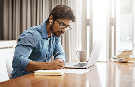 Cropped shot of a handsome young businessman working on his laptop in the office at home