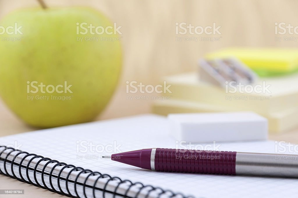 Writing equipment on desk with apple royalty-free stock photo