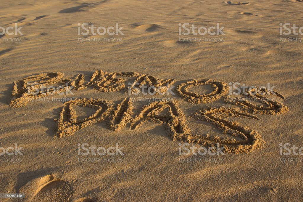 Writing 'Good morning' in spanish on sand stock photo